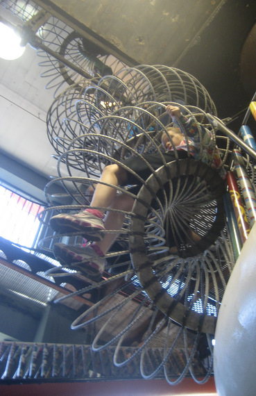 Kids crawling through metal spirals